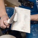 Painting worker repair wall using a paint spatula hand. Closeup photo